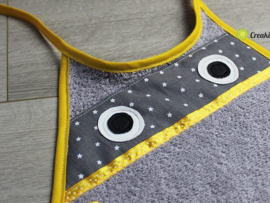 Bavoir curioso gris et jaune